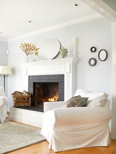 After: Charming, Classic Design  The now-striking fireplace surround boasts beautifully carved, white-painted moldings that frame the dark-painted fireplace bricks. The fireplace, perfectly proportioned crown moldings, white oak flooring, and a fresh, calming color palette fill the living room with charming, Cape Cod style.