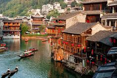 Chinese village on the water! You can see the stone base at the bottom of the houses, then three stories of wood. Lots of shutters, all open on this lovely day. Fantasy Village, Magic Places, Peles Castle, China Architecture, Architecture Design, Visit China, Beaux Villages, China Travel, Travel Europe