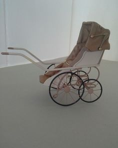 """A miniature pram made by artist Roberson. It measures 4"""" high x 5"""" long x apprix 2"""" wide. It is marked undrneath with the artists initials CYR. It is in very good condition. 