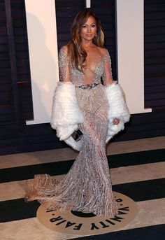 Jennifer Aniston showed some skin in a sheer beaded Versace dress on the Oscars red carpet.