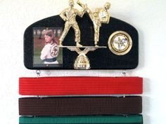 """Martial arts belt display with a KICK ! Midn. trophy dbl. by Dutch Touch Creations. $36.95. WE ARE STILL TRYING TO SHIP MOST DISPLAYS THE SAME DAY OR THE DAY AFTER THE ORDER IS PLACED. Fully expandable martial arts belt display ! Add as many slats as needed for your martial arts discipline ! Display features 12"""" x 6"""" display featuring a 3"""" x 4"""" acrylic picture window,(size is approximate). Martial arts decal on a gold holder. Martial arts kicking statue on pedestal. 10 slats pl..."""