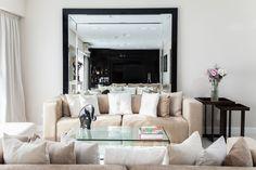 Living con sillones enfrentados con combinación de texturas en almohadones. Mesas ratonas de vidrio. Alfombra y espejo de pie con diseño de biseles. Mesas encastrables como mesas de arrime.