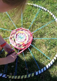 Constructing the hula hoop and adding patterns with tape.     The beginning of the weaving process, indoors.       Scrap fabric for we...