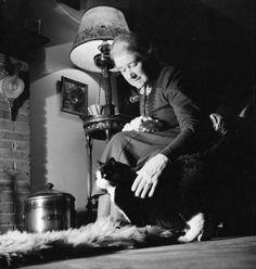 MRS BUGLER GOES TO WAR: EVERYDAY LIFE IN EAST DEAN, SUSSEX, ENGLAND, 1943. At the end of a long day, Mrs Bugler and her cat Tommy relax in front of the fire at her home in East Dean.