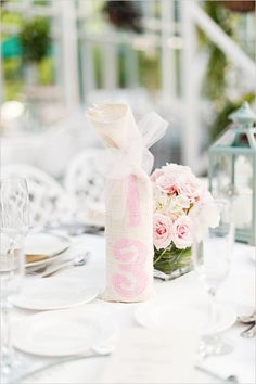 burlap painted wine bottles for table numbers #tablenumbers #pinkwedding http://www.weddingchicks.com/2012/11/06/pink-and-white-garden-wedding/