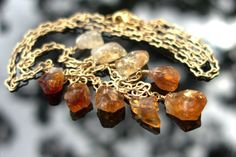 """IIII Raw Citrine Crystal Point Pendant by ShannonTamayoJewelry // 9 raw citrine crystal points, ranging in size from 3/8"""" long by 1/4"""" wide to 5/8"""" long by 3/8"""" wide, dangle from a 22"""" brushed gold plated chain, finished with lobster clasp. The citrine points are shaded, or, """"ombre"""", ranging from a pale buttercream yellow to a deep burnt amber."""