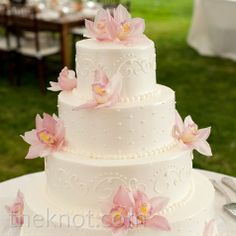 I think I would go with square layers and maybe a little color band between layers to match wedding colors bu i like the flowers and design in the frosting