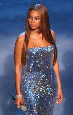 beyonce vestido preto bolsa dourado sapato azul | Dona Onça