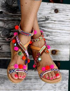 Entirely handmade greek sandals , embellished with colorful pom poms in hot pink and neon orange, bronze charms and friendship straps (not bonded but sewn) . These sandals feature a 1.5cm rubber sole for more comfort. A zipper is added for easier application.  A combination of strong colors, soft earthy leather tones and antique metals that will blow your mind! We were influenced by those nomad caravan travellers, gypsyish summer festivals with that intense rosewood smells and of course…