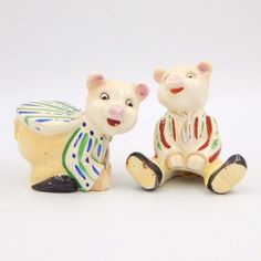 Vintage pre-owned glazed porcelain ceramic novelty figural collectible salt and pepper shakers set.  Two playful pigs are dressed up and posed in different positions.  One pig is seated and wearing red and green striped coat with tie, pants and shoes.  The other pig is bent over and wearing a blue and green striped coat with tie, pants and shoes. #Vintage #SaltandPepperShakers #Pig