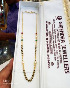 Beautiful gold long black bead haaram with pearl emerald and rubies.