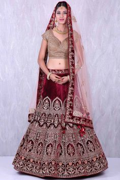 Let the wedding bells toll in this velvet lehenga in maroon and gold color. This outfit is designed with gota,zardosi,zari & sequins embroidery work all over the lehenga. As shown, maroon and gold velvet embroidered unstitched choli and peach color net em Bridal Lehenga Online, Indian Bridal Lehenga, Indian Bridal Outfits, Bridal Dresses, Indian Dresses, Pakistani Bridal, Lehenga Style, Net Lehenga, Anarkali