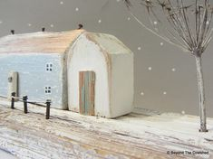 Snowy Christmas Cottage Pretty pastel cottage with frosty winter tree Handmade from Cornish driftwood Please note the little tree will be packed separately to keep it safe. 24 cm long x 8 cm wide x 13 cm high