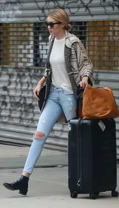 Gigi Hadid's casual style: a white T-shirt, distressed jeans, black booties, a Tory Burch sweater, and some tortoise shell sunglasses.