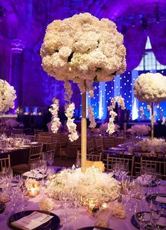 Can find tall wooden spools, spray paint and attach fake flowers on top and base of center piece