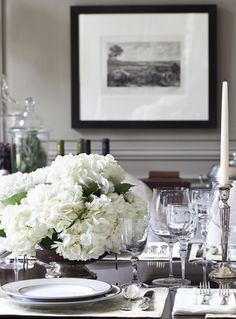 White hydrangeas are pretty but not overpowering. Soft pewter silver-banded plates complement the wall colour, and simple tapered candles are perfect year-round. Kitchen table
