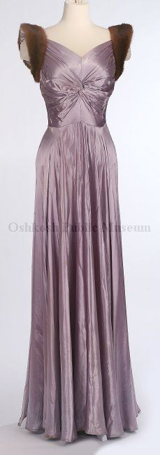 Circa 1940 evening gown of lavender silk with V-neck bodice; fabric from armhole twisted in front and extending back to side seams, sleeveless with mink fur trim around armholes; skirt is fitted at waist and flares out to form a full circle at hem; back bodice forms a deep V-twist.