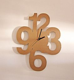"Reloj pared ""números"" (incluye máquina c/agujas negras). Material: cartón corrugado doble-triple 6 mm espesor Medidas: diámetro 23 cm Opcional: aplicación barniz ecológico o papel color:"