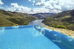 Infinity pool high up on a hill overlooking a valley and river.