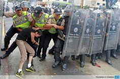An anti-government activist clashes with riot police during a protest in Caracas, Venezuela