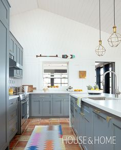 To simplify this kitchen, designer Virginie Martocq installed cabinets with Shaker-style doors, as well as delicate brass pendants over the island. | Photographer: Kim Jeffery