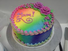 A simple two-tier cake made interesting with a rainbow airbrush pattern and a striped border and roses made from three different colors in one bag.