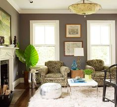 A Mix-and-Match of Styles    The dark gray walls add drama to this living room. The color, inspired by the bark on the dense trees that surround the home, lets the wooded side table and frames stand out. Other elements, such as the metallic garden stool and ottoman, bring out the wall's cool undertones. This room is a mixture of styles that all work together thanks to the wall's versatile hue.