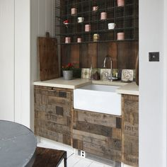 Rustic kitchen, white tongue and groove, white floorboards, white belfast sink, dark wood planks behind sink with row of old tiles, wall hung black wire racking with mugs, tin pot with red flowers, wood butchers board, kitchen doors made from fruit boxes, kitchen units from Wickes, old dark wood stool, black table
