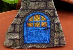 A welcoming glow of light shines through the window of this charming little blue wooden door. It's sure to attract all the wee magical folk to your home & garden!  Hand painted in fine detail on a small shard of natural stone, this enchanted door is the perfect size for display in potted plants, ...