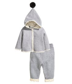BABY EXCLUSIVE/CONSCIOUS. Set with jacket and pants in quilted jersey made from an organic cotton blend. Jacket with long sleeves, lined hood with pompom at top,  snap fasteners at front, and no lining. Pants with wide, foldover ribbing at waist. Patterned trim at hems, visible when pant legs are rolled.