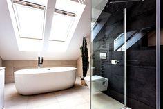 Die freistehende Badewanne zusammen mit der Schieferwand sind absolute Hingucker