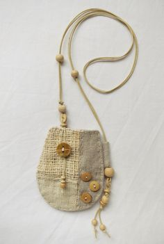 A beautiful patchwork talisman pouch, made using hand woven hemp, indian cotton and natural linen. It has hand stitched details around the edge and the