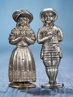 TWO SILVER NEEDLE CASES AS MAN AND WOMAN IN TRADITIONAL COSTUMES The matching silver pair depict a hollow-bodied man and woman with well-defined traditional costumes,opening at the center for access to the interior. с 1800