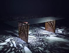 The Riddled table by Steven Holl for Horm. Glass and wood, the cut-outs in the legs of the table cast a beautiful pattern of light around.