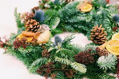 Christmas wreath detail - this Christmas wreath was made at a corporate wreath workshop put on by Jennifer Pinder. Glitter birds, pinecones, thistles, skimmia, oranges and more! xx