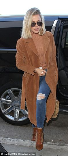 Fashionista! The Keeping Up with the Kardashians star made a fashion statement in a long suede brown coat as she entered the busy terminal