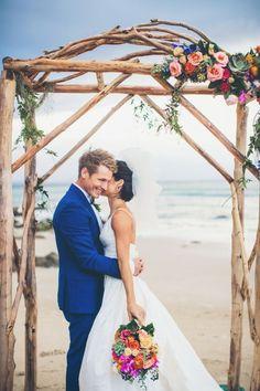 Gorgeous floral arch: http://www.stylemepretty.com/australia-weddings/new-south-wales-au/byron-bay/2015/08/14/elegant-colorful-beach-wedding/ | Photography: Ivy Road - http://ivyroadphotography.com.au/