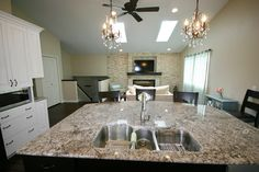 Kitchen Remodel with an island sink, 3 bowl kitchen sink, granite countertops, white cabinetry, stone fireplace face, vaulted ceilings, skylights.