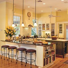 Softer yellow kitchen; lighting, bookcase, glass front cabinets, backsplash, flooring