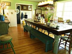 Farmouse table + rustic benches + mismatched chairs + eclectic styling + open suitcase on the buffet