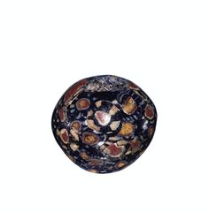 #Mosaic #Deep blue opaque (matrix); white, red, and yellow, all opaque (cane slices). Slices of preformed canes inlaid in matrix formed around rod. Biconical bead tending toward spheroid, with circular perforation (D. 0.65 cm). Blue matrix embedded with numerous slices and chips of polychrome canes, of which two types occur: (1) with circular yellow core surrounded by concentric circles of red, white, and blue and white stripes; (2) with circular red core surrounded by concentric bands of…