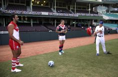 The Los Angeles Dodgers' Clayton Kershaw, right, passes an Australian rules football at the Sydney Cricket Ground in Sydney, Wednesday, March 19, 2014. The MLB season-opening two-game series between the Dodgers and Diamondbacks in Sydney will be played this weekend. (AP Photo/Rick Rycroft)