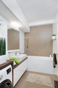 Koupelna – kombinace bílé a hnědé je nadčasová, lesklé obklady (RAKO, série Defile) dodávají prostoru luxusní charakter. Nábytek byl vyrobený na míru, drobné doplňky jsou od Sapho.