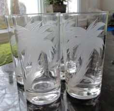 Set of four clear vintage highball or tumbler glasses with etched palm trees. Stamped on bottom by Federal Glass Company. No chips, cracks or clouding. Excellent condition.  Im GUESSING these were probably made in the 1960s or 70s. They are each 5 1/8 tall and 2 1/2 wide. I havent measured, but I guess they hold about 8oz of liquid. These are PERFECT for summer entertaining, beach homes or for those who just love vintage barware. When you see an F within a shield, that is the mark o...