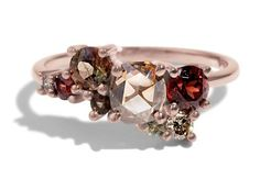 This Custom Cluster ring features a .69ct high clarity free form champagne rose cut diamond from Australia and is surrounded by a mixture of champagne diamonds, sapphires, garnets and andalusite. Shown in high polish 14kt rose gold.