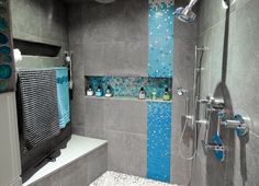 The decorative blue mosaic tile goes all the way up the ceiling replicating being caught in a wave in the ocean. #shower #shampooniche #blue