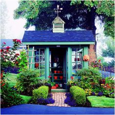 Beautiful blue potting shed landscaped.