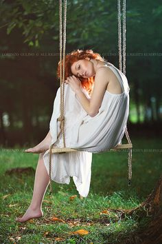 Beautiful sad woman on a swing in the forest . Romantic portrait  Model : Lucia Manetti