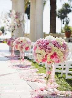 Beautiful round rose and hydrangea arrangements set on vases that can be moved inside and used as centerpieces.