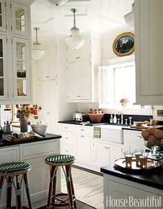 Cabinets right to the ceiling to maximize storage. I love the antique looking light fixtures.